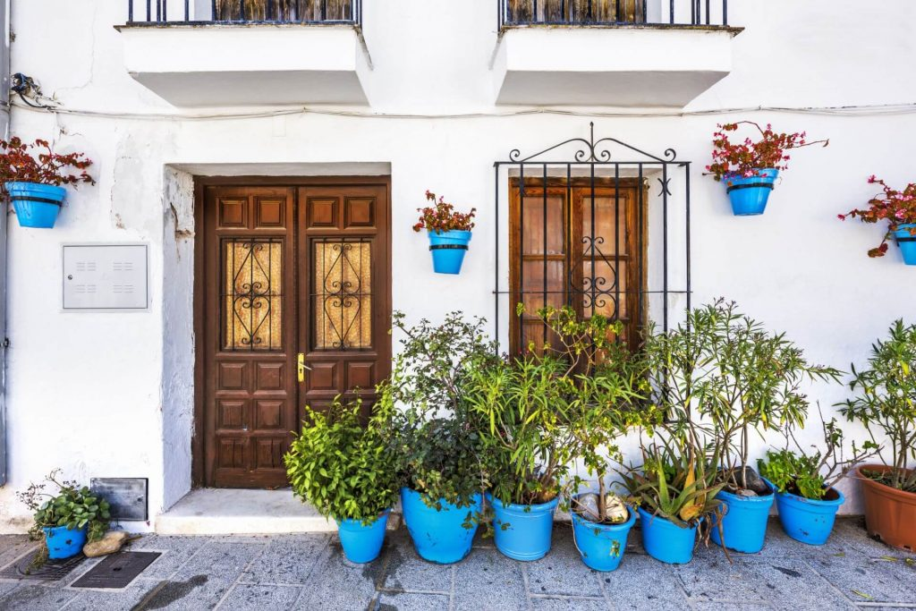 Facade of house with flowers in blue pots in Mijas